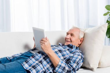 side view of cheerful senior man lying on sofa and using tablet at home