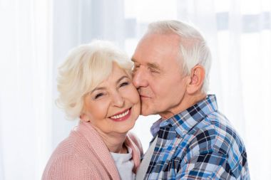 portrait of senior man kissing happy wife that looking at camera