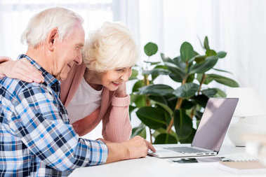 side view of smiling senior couple using laptop together at home