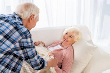 senior man covering happy wife with blanket on cozy couch