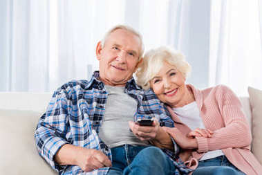 senior couple with remote control watching tv on couch