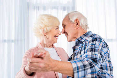 side view of smiling senior couple dancing together at home