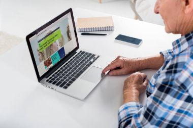 Partial view of senior man working on laptop with bbc logo at table with notebook at home stock vector