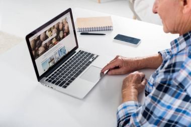 partial view of senior man working on laptop with depositphotos logo at table with notebook at home