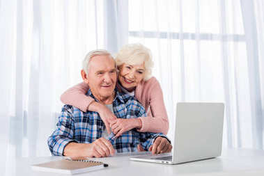 portrait of cheerful senior couple using laptop together at home