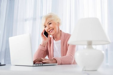 portrait of smiling senior woman talking on smartphone while using laptop at home