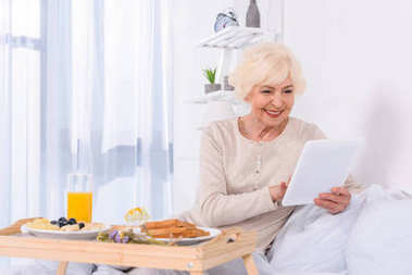 happy senior woman with breakfast in bed using tablet at home