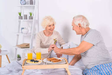 senior man presenting flowers to wife while having breakfast in bed together at home