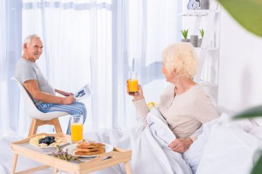 side view of senior woman having breakfast in bed while husband wit newspaper sitting at table  in bedroom