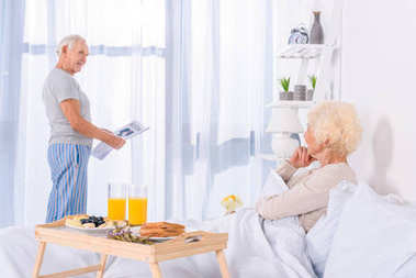 partial view of senior woman looking at husband with newspaper at window at home