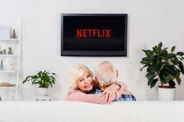 senior couple embracing on couch in front of tv with netflix logo on screen