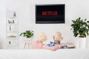 back view of senior couple watching netflix on tv at home