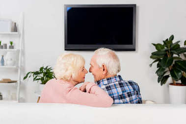 senior couple sitting on couch in front of tv at home