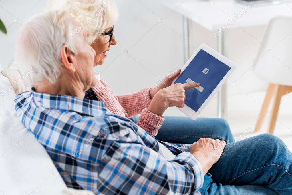 side view of senior couple using digital tablet with facebook logo together