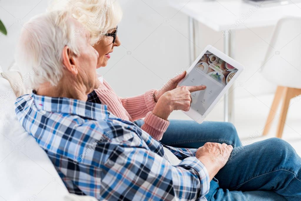 side view of senior couple using digital tablet with foursquare logo together