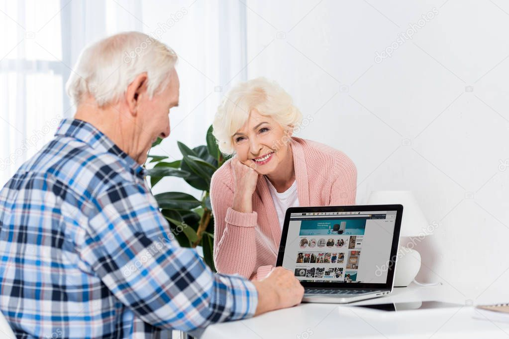 portrait of senior wife looking at husband using laptop at home