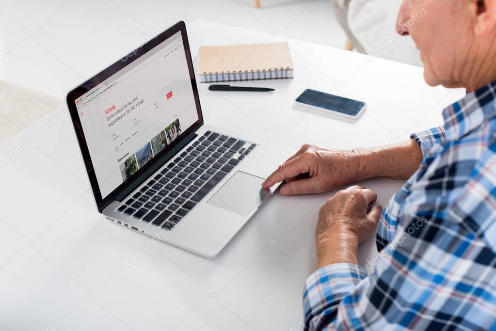 partial view of senior man sitting at table and using laptop with airbnb logo