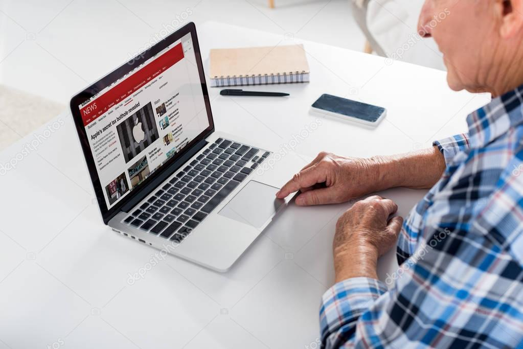 partial view of senior man sitting at table and using laptop with bbc logo