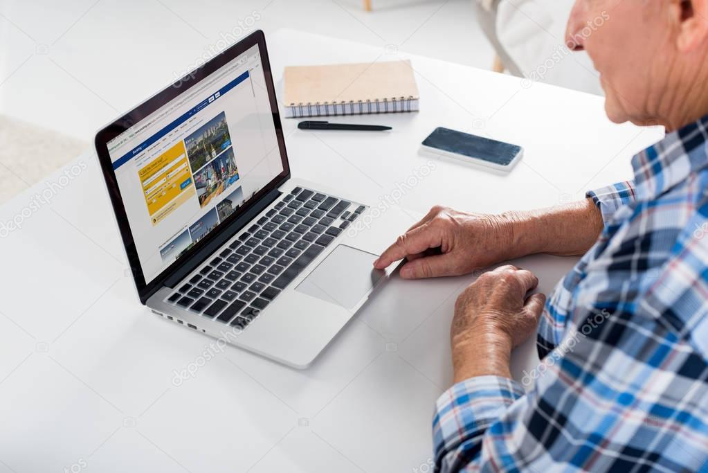partial view of senior man sitting at table and using laptop with booking com logo