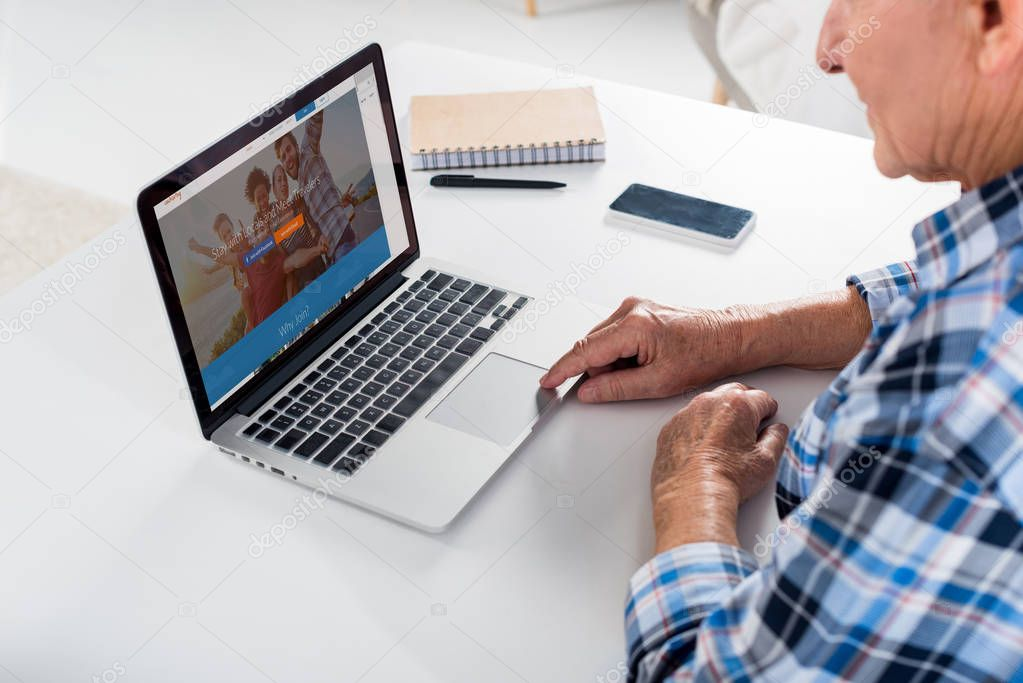 partial view of senior man working on laptop at table with notebook at home