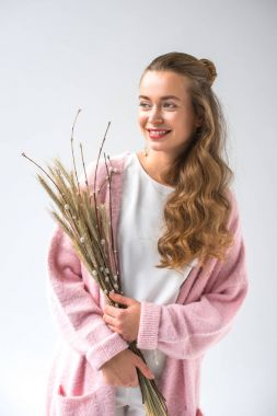 smiling woman holding bunch of willow tree branches and spikelets isolated on white