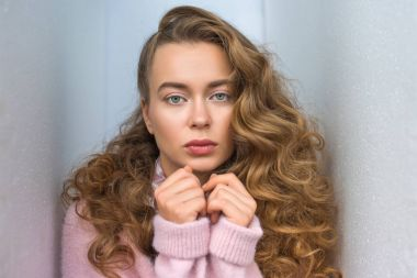 portrait of serious girl with long curly hair looking at camera and standing between walls