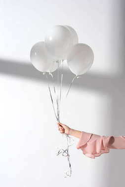 cropped image of girl holding bundle of balloons with helium in hand