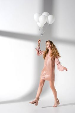 Smiling girl with curly hair going with white balloons