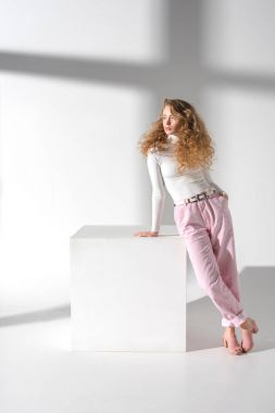 Stylish confident woman standing and leaning on white cube