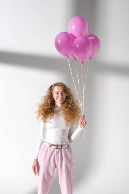 happy woman standing with balloons with helium and looking at camera