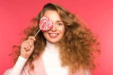 smiling girl covering eye with heart shaped lollipop isolated on red