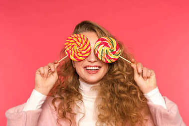 happy girl covering eyes with round lollipops isolated on red