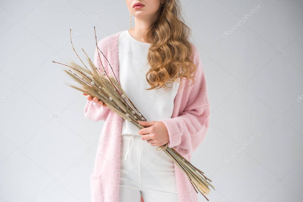 cropped image of stylish woman holding bunch of willow tree branches and spikelets isolated on white