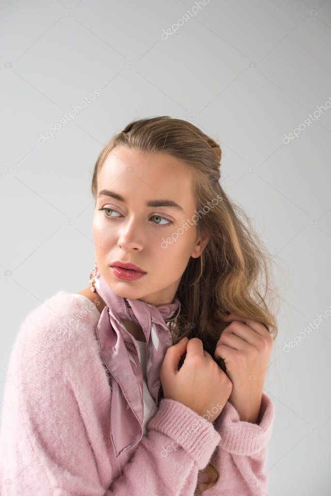 attractive woman in pink shirt and scarf looking away isolated on gray