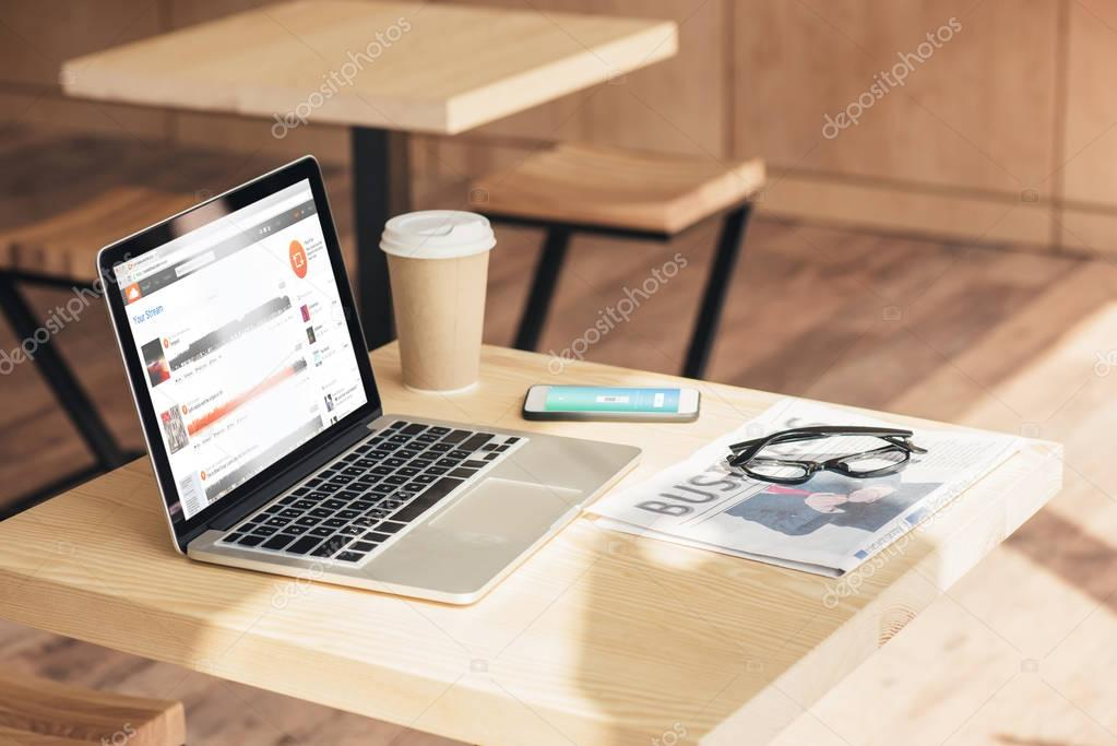 laptop with soundcloud, smartphone with uber and business newspaper on table in coffee shop