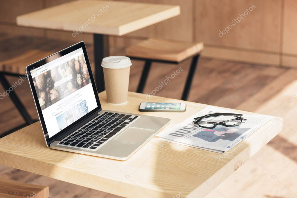 laptop with depositphotos, smartphone and business newspaper on table in coffee shop