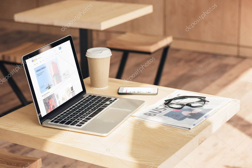 laptop with ebay website, smartphone and business newspaper on table in coffee shop