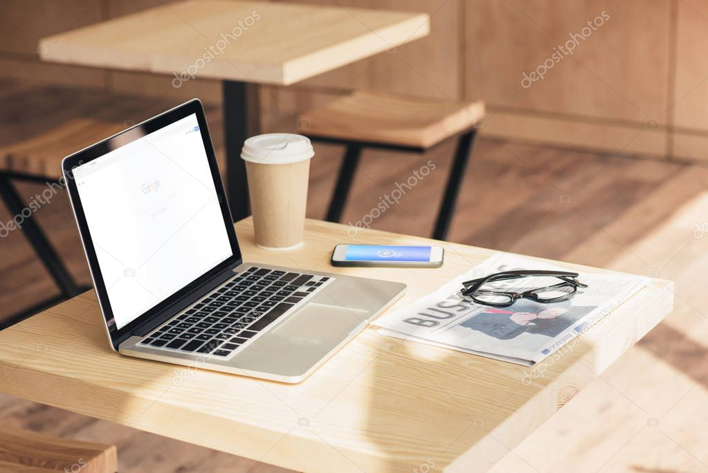 laptop with google website, smartphone and business newspaper on table in coffee shop
