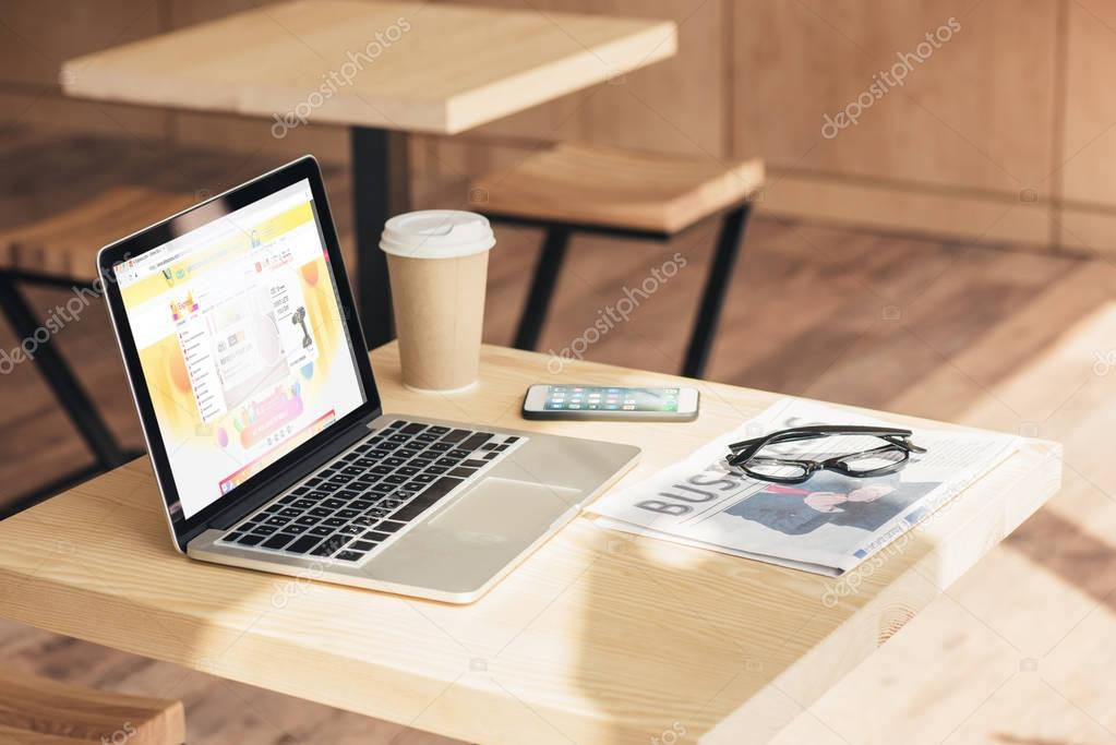 laptop with aliexpress website, smartphone and business newspaper on table in coffee shop