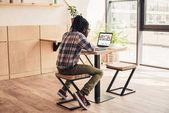az afrikai-amerikai ember használ laptop-val depositphotos weboldal kávézóban hátulnézet