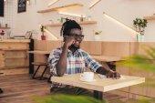afro-amerikai ember beszél a smartphone és a kávéfogyasztás kávézó