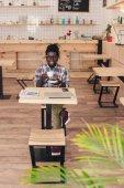 mosolyogva afro-amerikai ember iszik kávé, kávézó asztal