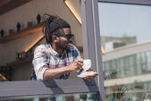 cheerful african american man drinking coffee in cafe