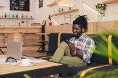 vidám afro-amerikai ember használ smartphone és a laptop a kávézóban