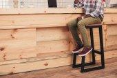 Fotografie Unterteil eines afrikanisch-amerikanischen Mannes, der an der Theke eines Cafés sitzt