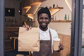 Fotografie lächelnd afroamerikanische Barista halten Einweg-Tasse Kaffee und Kraft-Paket