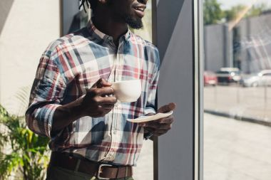 cropped view of african american man drinking coffee while standing at window