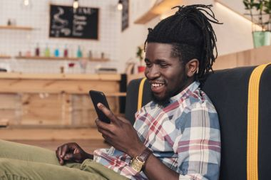 smiling african american man using smartphone in cafe