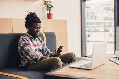 african american man using smartphone and laptop in coffee shop
