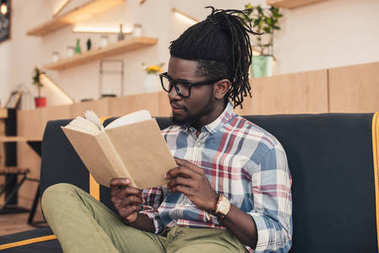 african american man reading book while sitting on sofa in cafe